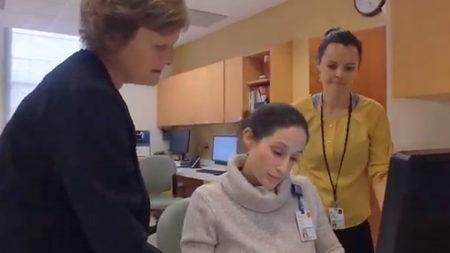 Three women gathered around a computer