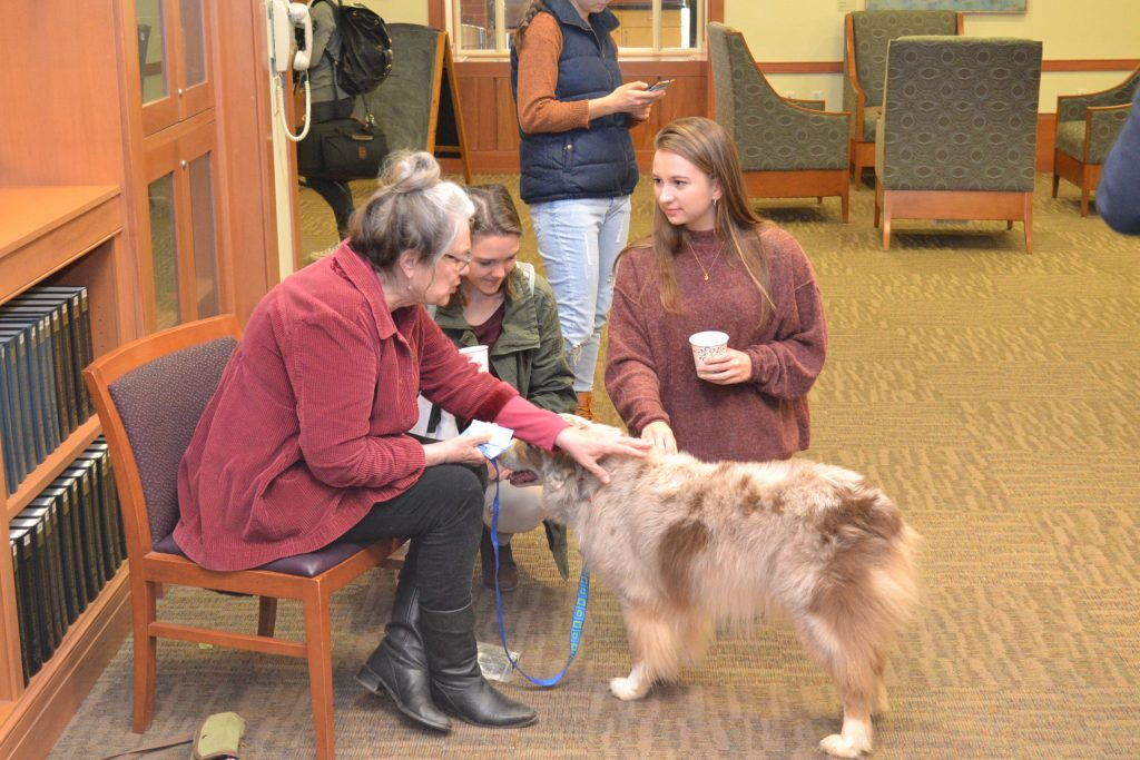 Students talking to volunteer about the therapy dog program.